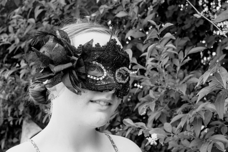 Beautiful girl in black mask masquerade ball